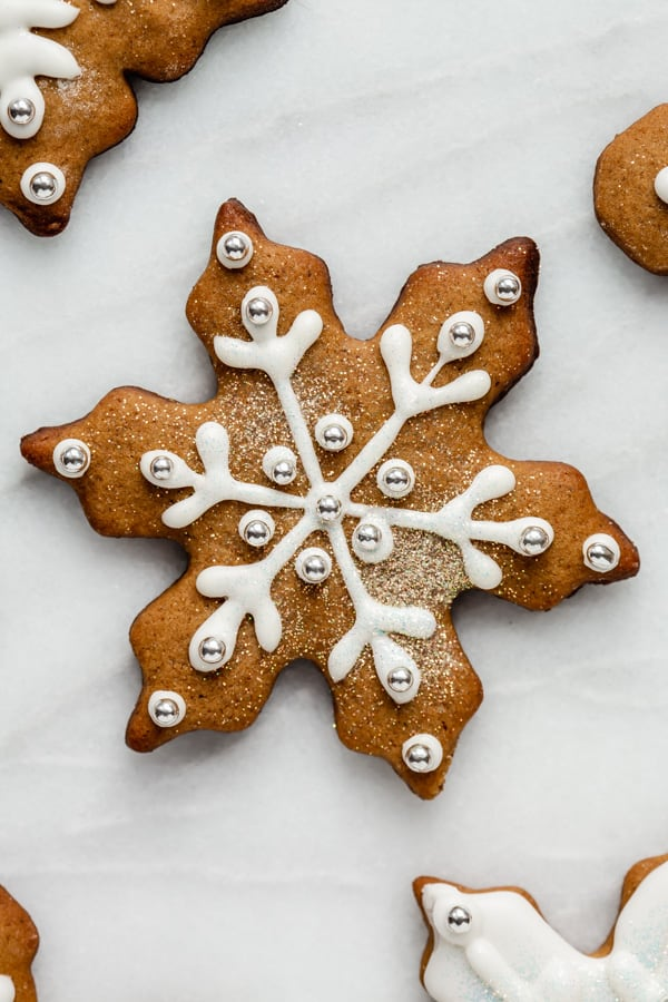 a snowflake gingerbread cookie topped with icing and glitter