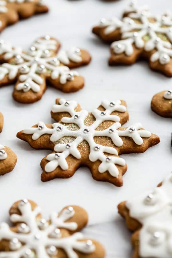 snowflake gingerbread cookies with royal icing on a marble board