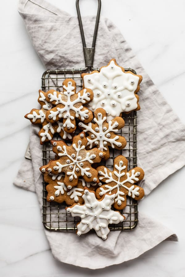 snowflake gingerbread cookies on a cooling rack and napkin