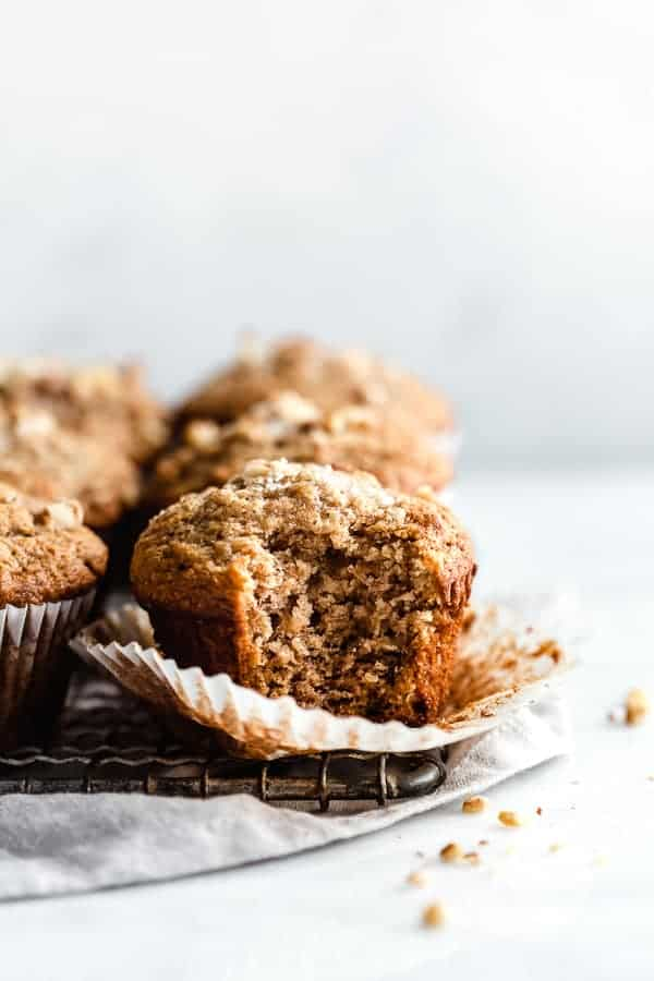 cooling rack filled with healthy breakfast banana nut muffins, with a bite taken out of one muffin on top of a grey linen
