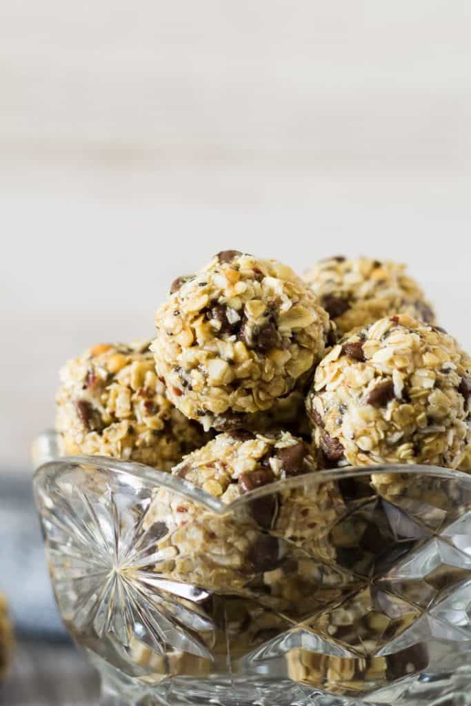 healthy breakfast energy bites made of balls of oats with chocolate chips and peanut butter, in a glass crystal bowl