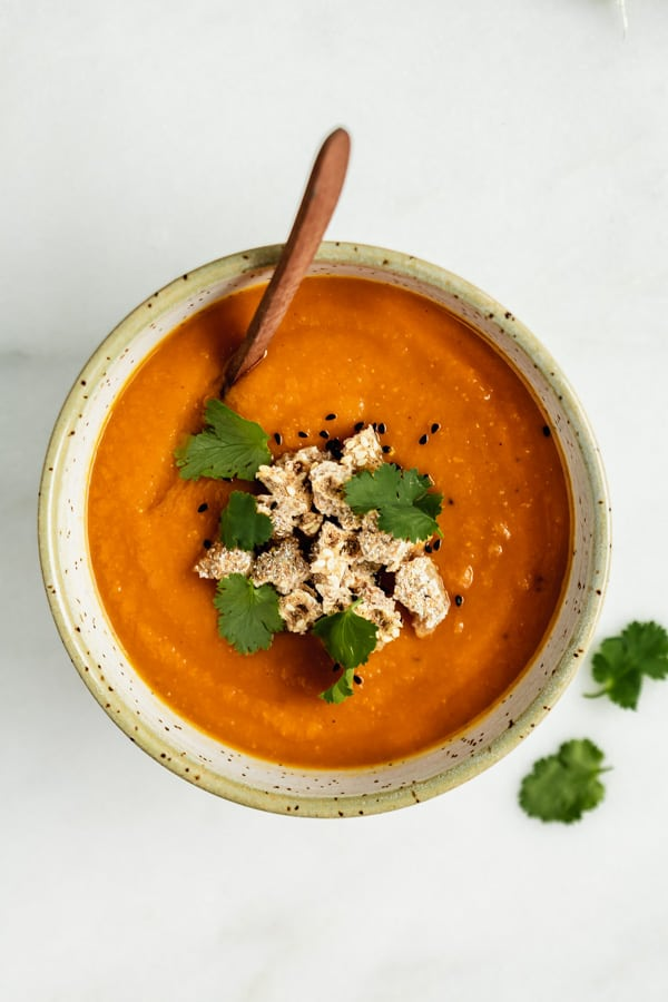 a bowl of orange soup with cilantro on the side