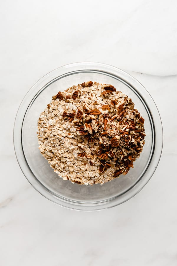 oats and pecans in a clear mixing bowl