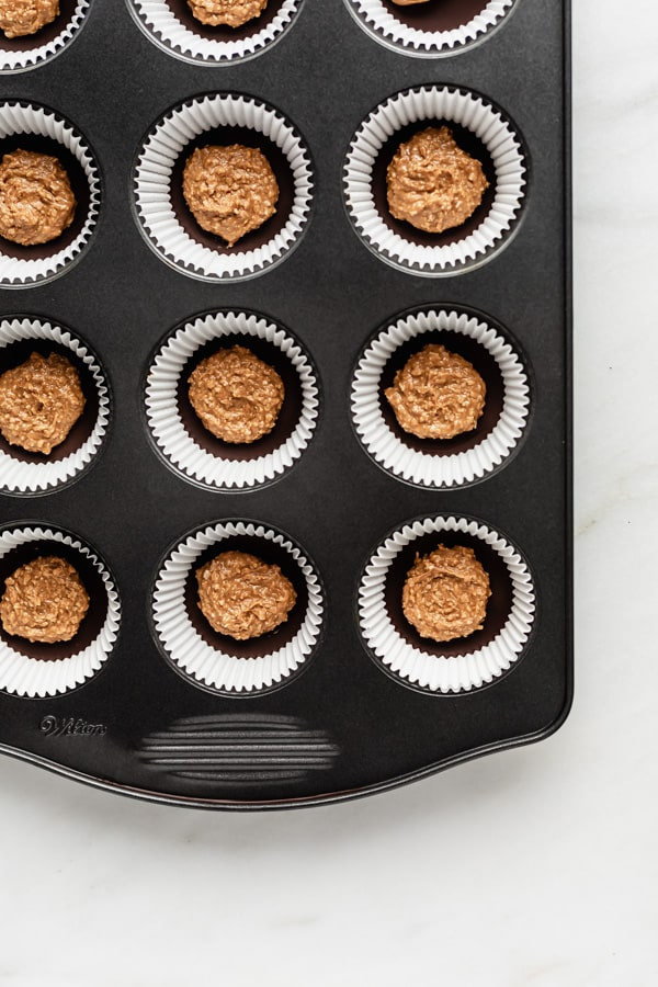 a muffin pan filled with muffin liners, a layer of chocolate and a scoop of almond butter