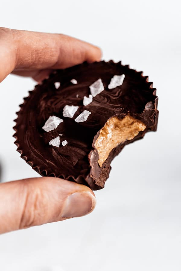 A hand holding a dark chocolate almond butter cup with a bite taken out of it