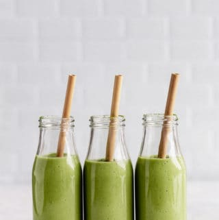three bottles of matcha green tea smoothies with bamboo straws in them