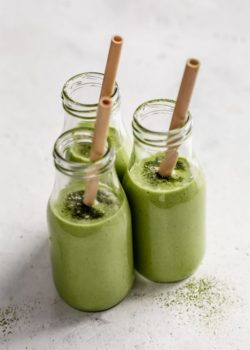 three jars of matcha green tea smoothies topped with matcha powder and straws in them