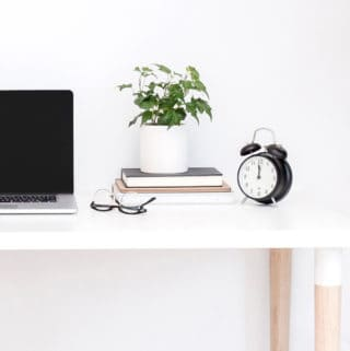 A clock, stack of books and plant on a white desk