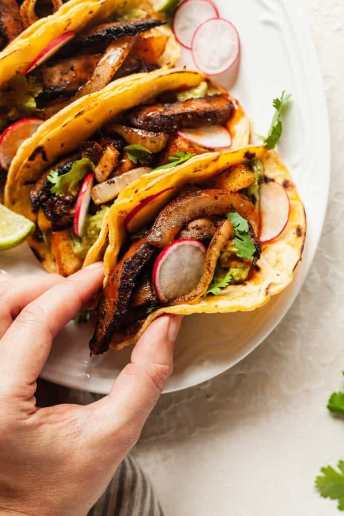 hand reaching for a taco filled with vegetables, cilantro, and sliced radishes lined up on a white serving platter with lime wedges for date night
