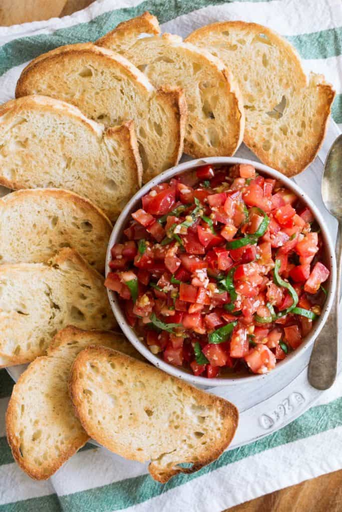tomato bruschetta in a white bowl surrounded by toasted bread against a green and white linen