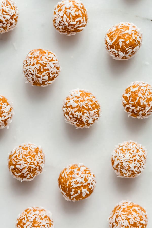 apricot energy balls covered in shredded coconut on a marble board