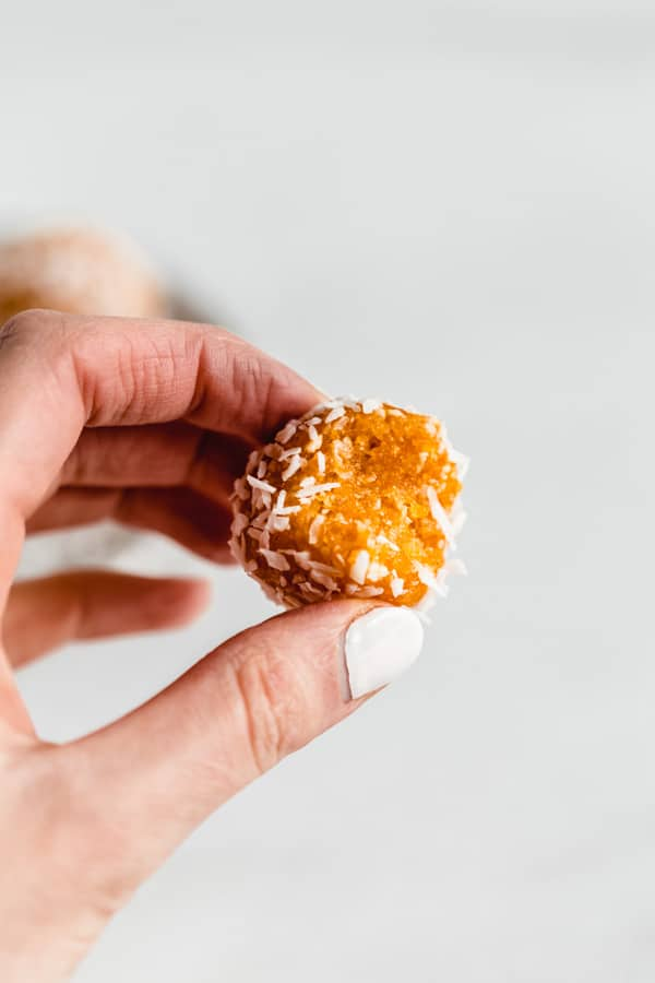 a hand holding an apricot energy ball with a bite taken out of it