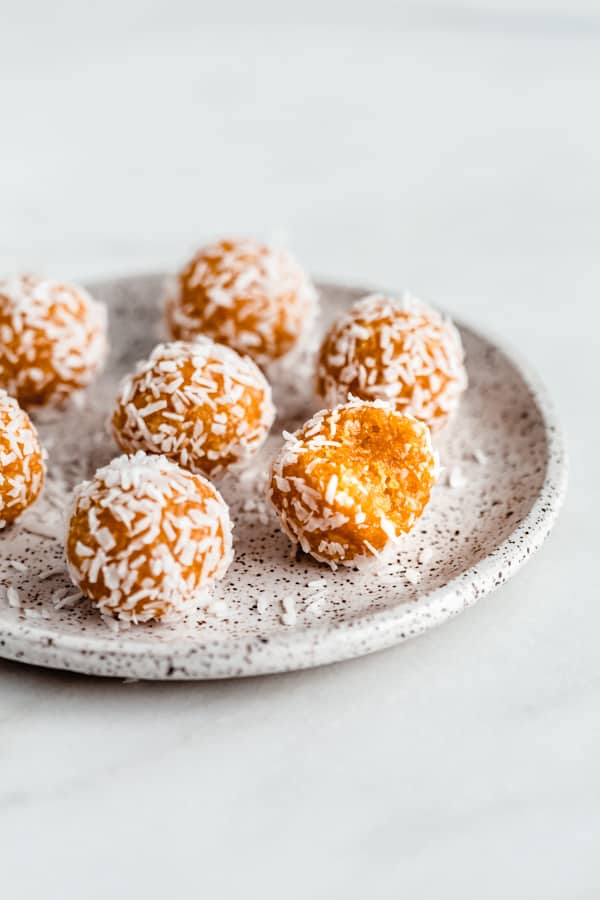 Apricot energy balls on a speckled ceramic plate