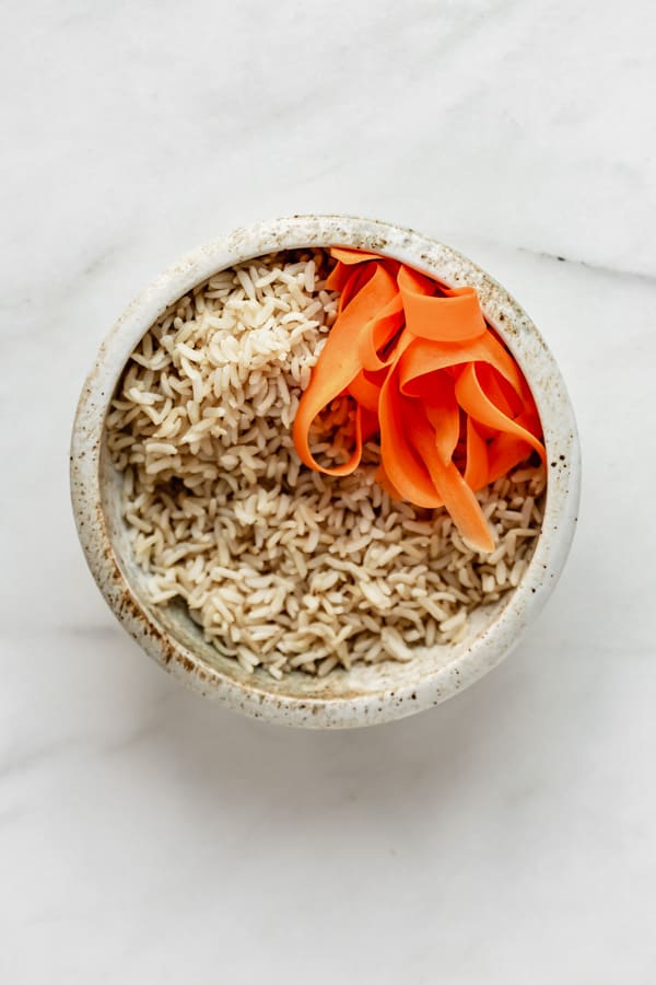 a ceramic bowl with brown rice and carrots in it