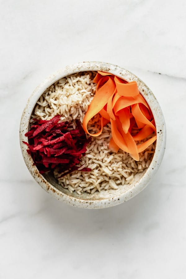a white ceramic bowl with brown rice, shredded beets and carrots