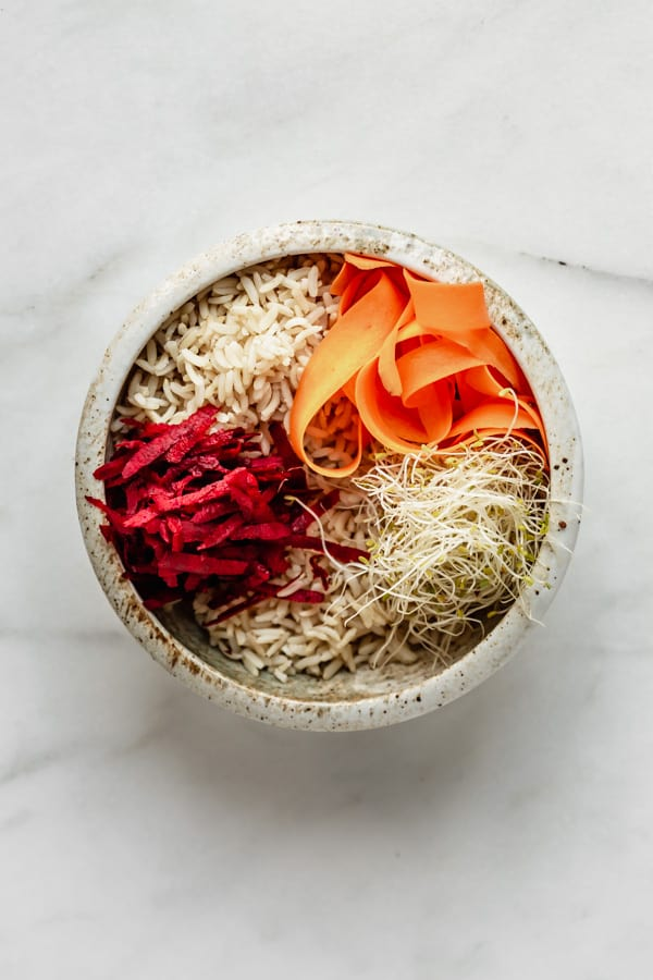 a white ceramic bowl with brown rice, beets, carrots and sprouts in it