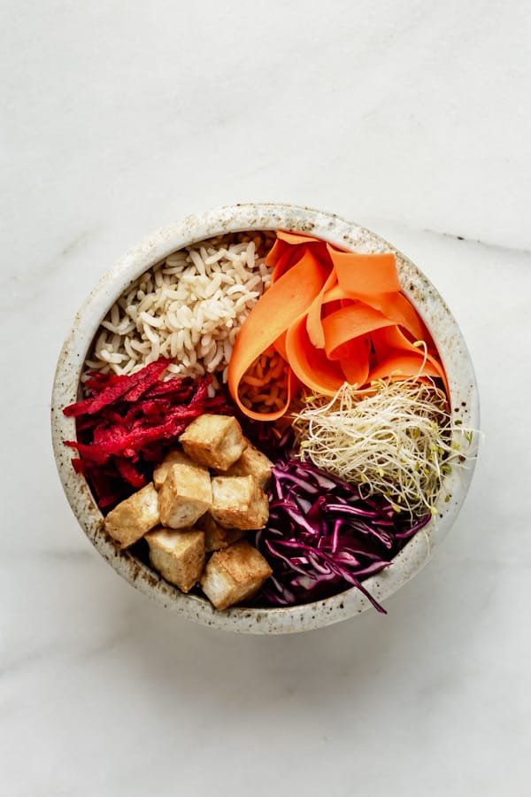 a white ceramic bowl with brown rice, tofu and veggies in it