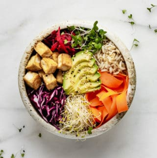 a ceramic bowl with avocado, veggies, tofu and brown rice