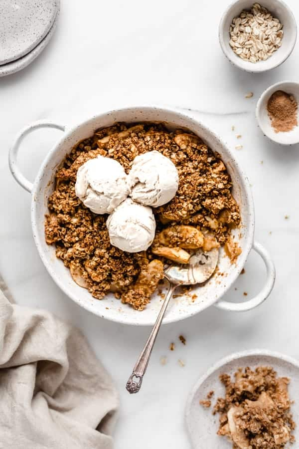 one silver serving spatula sitting underneath a layer of healthy apple crisp in a white baking dish, topped with three scoops of ice cream and surrounded by oats and brown sugar and a tan linen