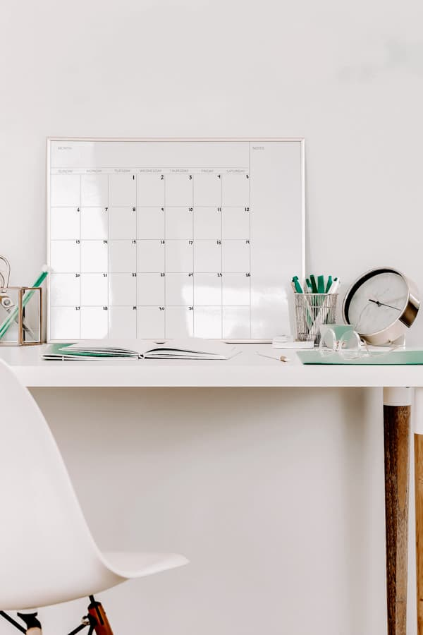 A calendar and notebook on a white desk