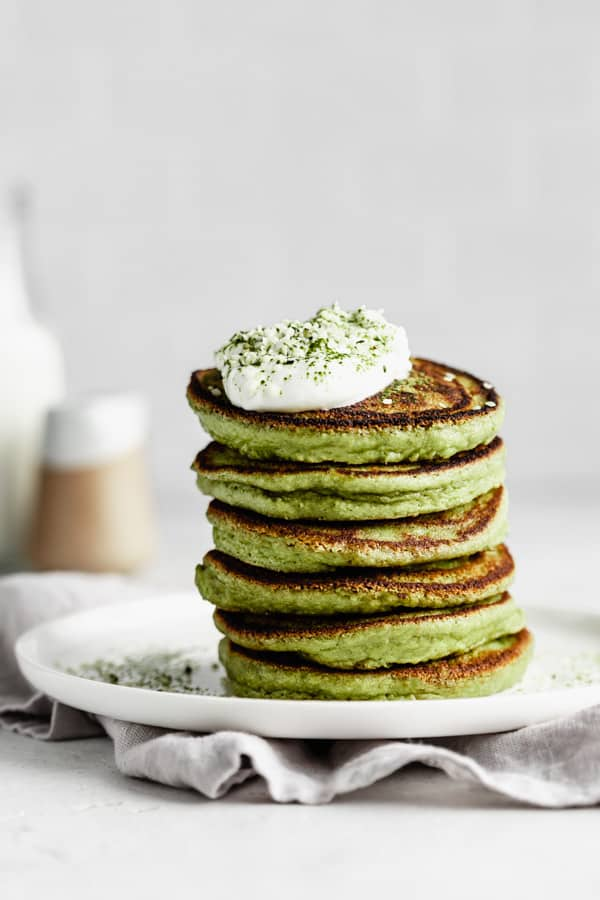 a stack of matcha pancakes topped with yogurt