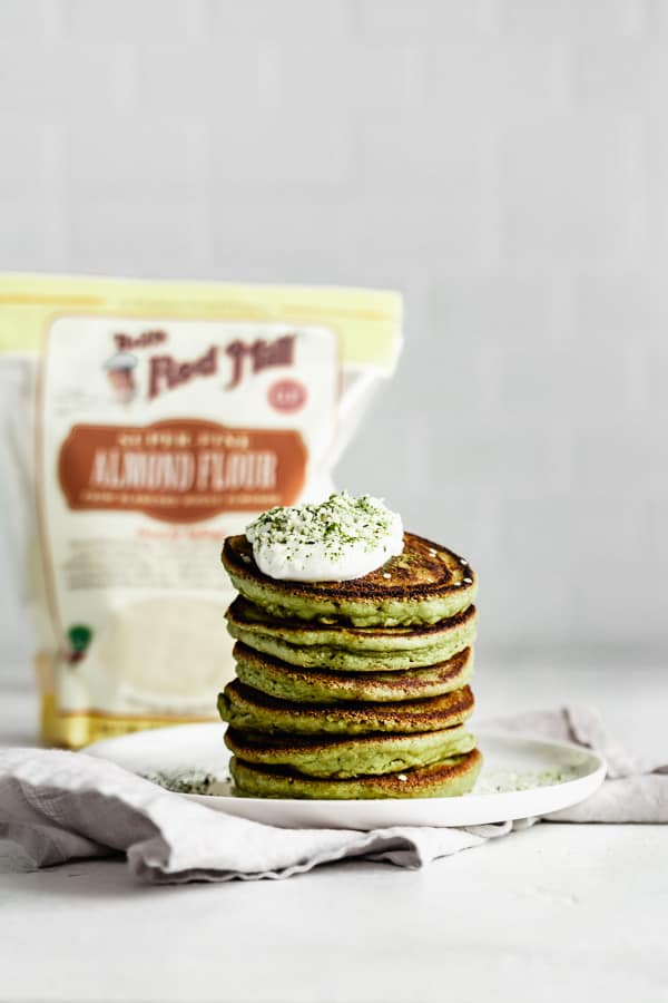 a stack of matcha pancakes with a pack of almond flour in the background