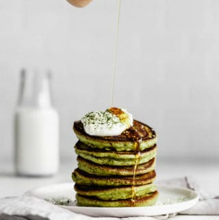 a hand pouring syrup onto a stack of matcha pancakes
