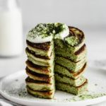 a stack of matcha pancakes with a cut taken out of it