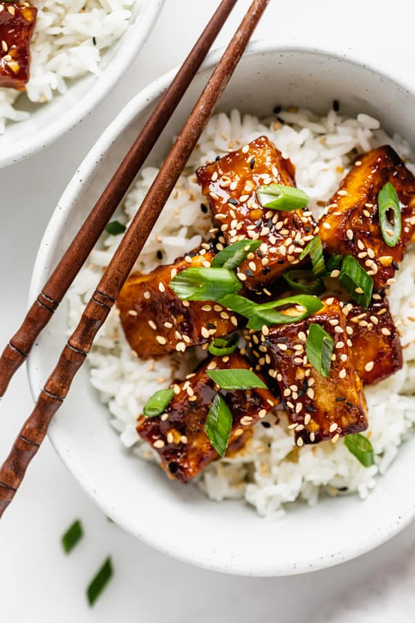 rice in a bowl with orange tofu green onions and sesame seeds