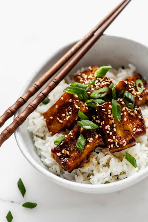 orange tofu in a bowl topped with green onions