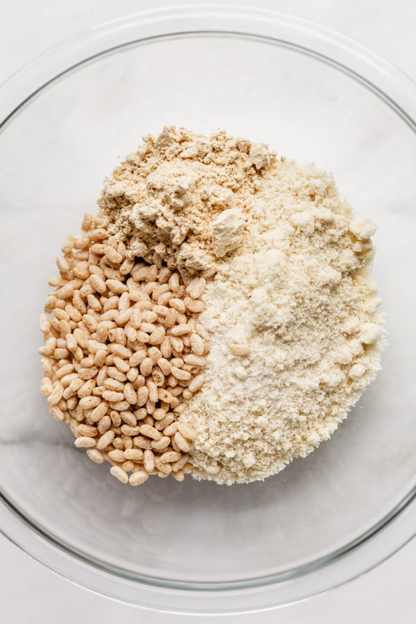 a clear mixing bowl with almond flour, protein powder and rice crisps in it