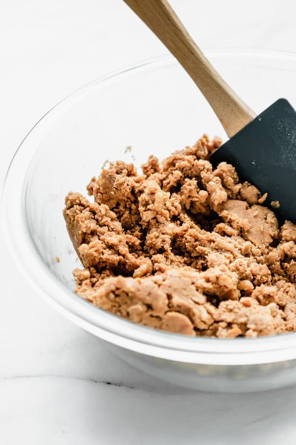 a clear mixing bowl with peanut butter protein bar dough in it and a spatula
