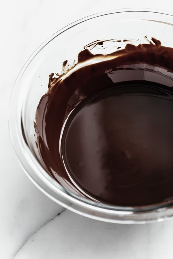 a clear bowl with melted dark chocolate in it