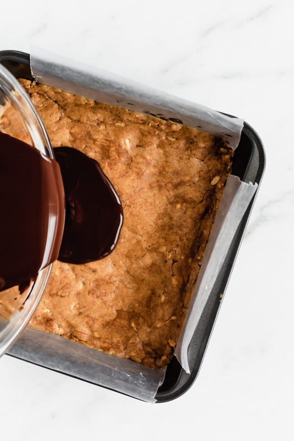 chocolate being poured into an 8x8 inch pan of peanut butter protein bars