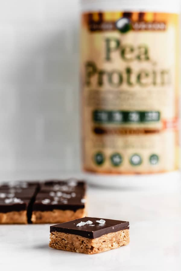 Peanut butter protein bars on a marble board with a container of protein powder in the back