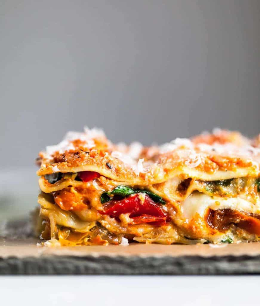 roasted vegetable lasagna date night recipe topped with cheese on a wooden board against a grey backdrop