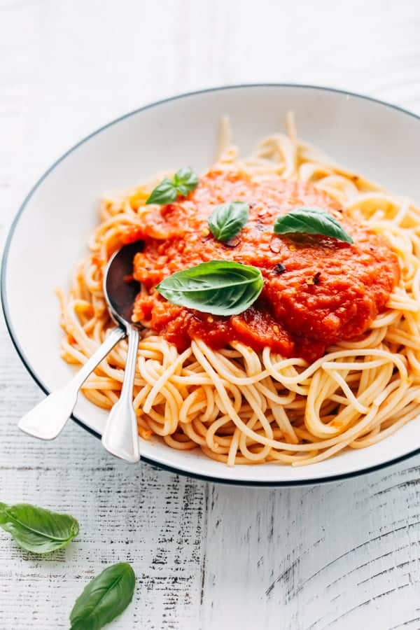 two silver spoons in a bowl of spaghetti covered with homemade tomato sauce and fresh basil leaves for an easy date night dinner