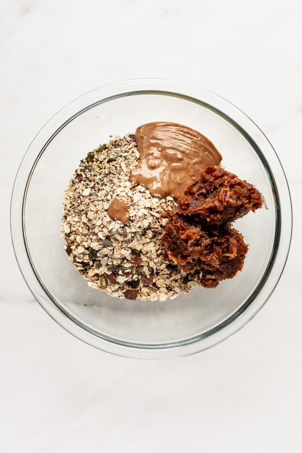 A clear mixing bowl with oats, nuts, date paste and almond butter in it