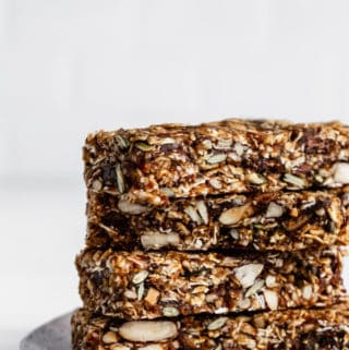 a stack of four superfood granola bars on a white ceramic plate