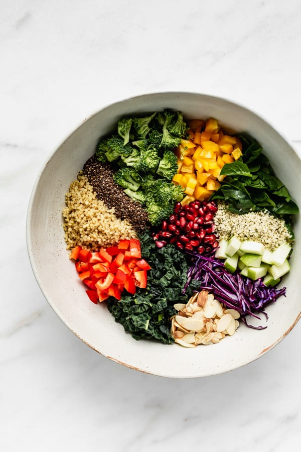 a bowl of ingredients for a superfood salad on a marble counter