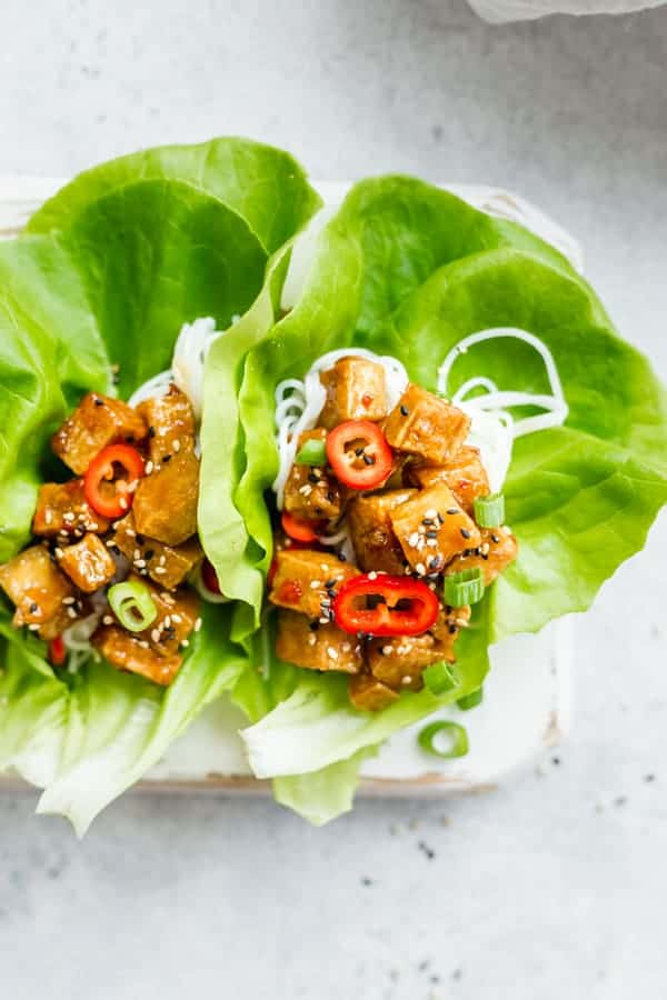 sweet chili tofu with green onions and peppers in butter lettuce cups with rice noodles on a plate on a grey backdrop