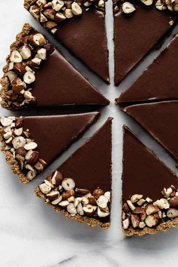 close up shot of chocolate tart slices covered with chopped hazelnuts arranged in a circle on a marble pastry board
