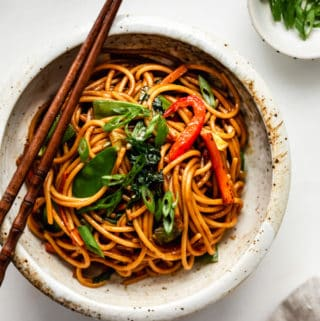 vegetable lo mein in a ceramic bowl with a side of sliced green onions