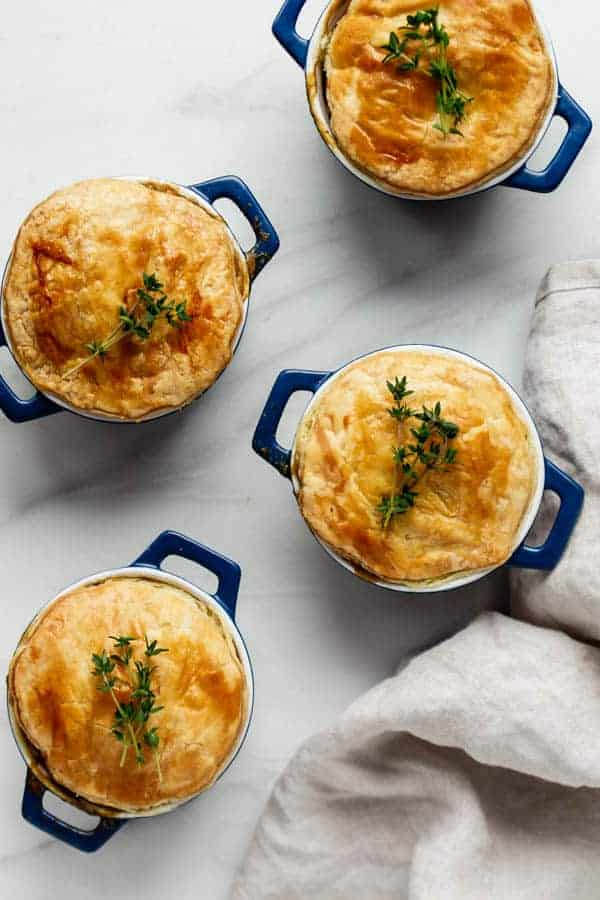 veggie pot pies topped with fresh thyme in blue mini dutch ovens, with crunchy puff pastry crust on a marble counter