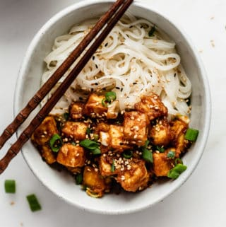 a bowl of noodles topped with peanut butte tofu, sesame seeds and green onions