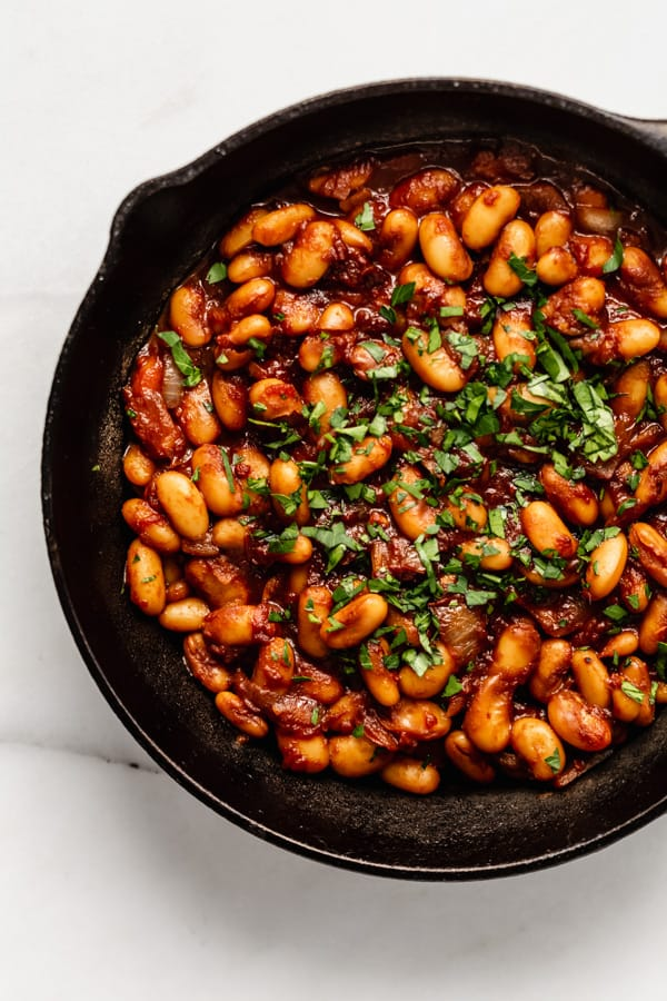 maple baked beans in a cast iron skillet topped with parsley