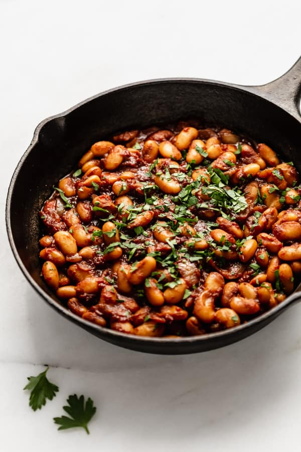 a close up of maple baked beans in a cast iron skillet