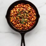 a cast iron skillet of maple baked beans on a marble counter