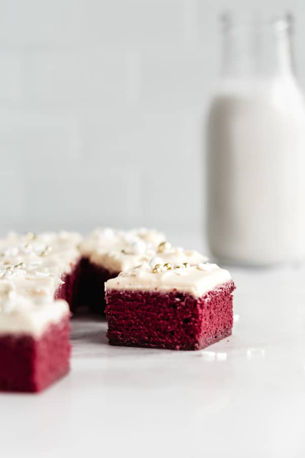 Red velvet brownies topped with icing and white and gold sprinkles on a marble board