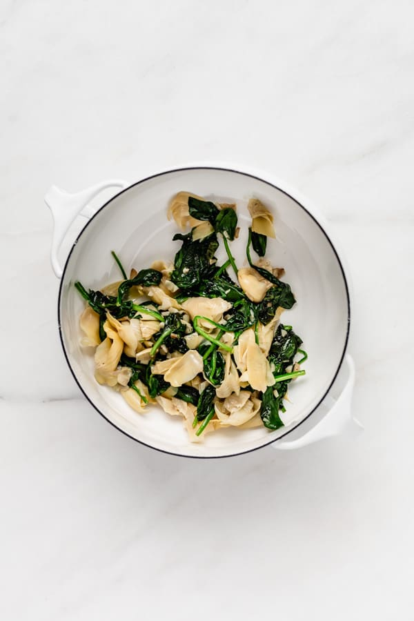 A white pot with spinach and artichoke hearts in it